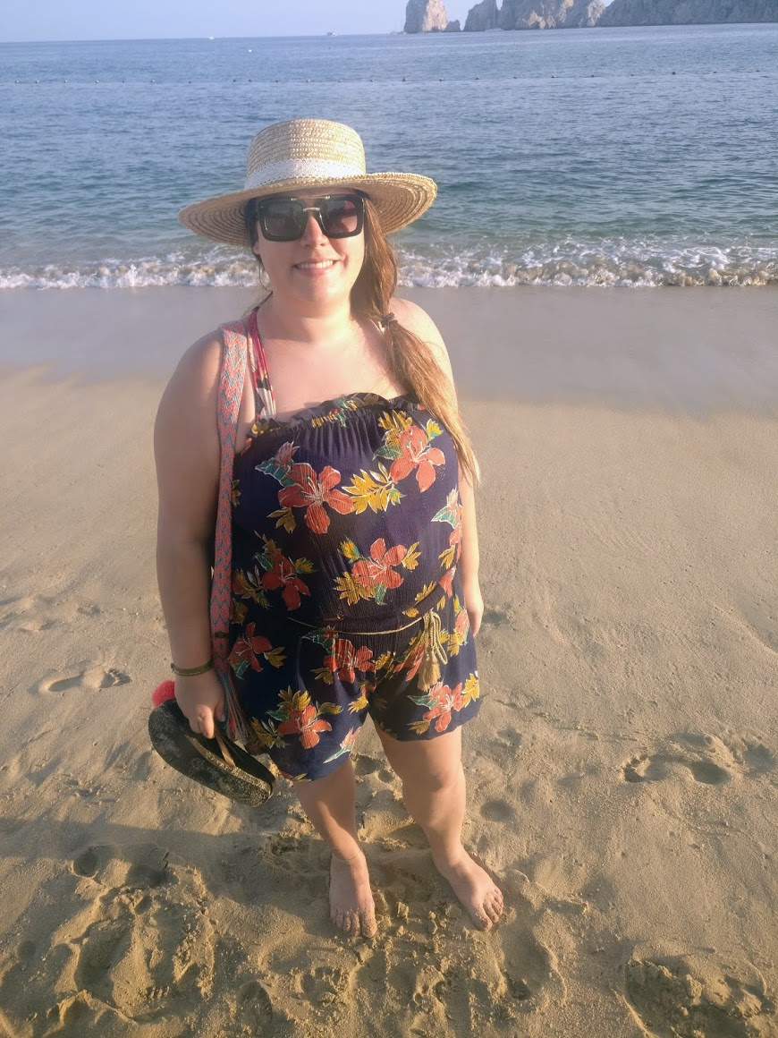 Alicia is on the Cabo San Lucas beach wearing a Forever 21 romper and ASOS straw panama hat.